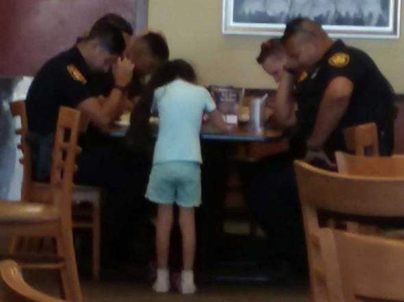 Viral foto de niña orando por policías que lamentaban muerte de colega